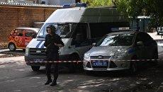 Сотрудник полиции у магазина Дикси на улице Большая Академическая в Москве, где неизвестный незаконно удерживает работника магазина. 1 июля 2018