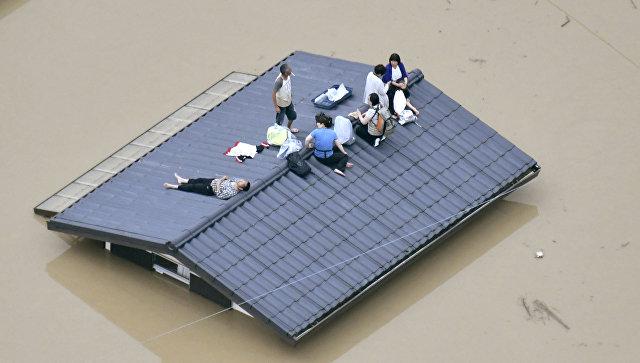 Жители города Курасики ждут спасателей во время наводнения в Японии. 7 июля 2018 года