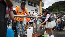 Местные жители получают питьевую воду в городе Михара, префектура Хиросима, Япония. 9 июля 2018 года