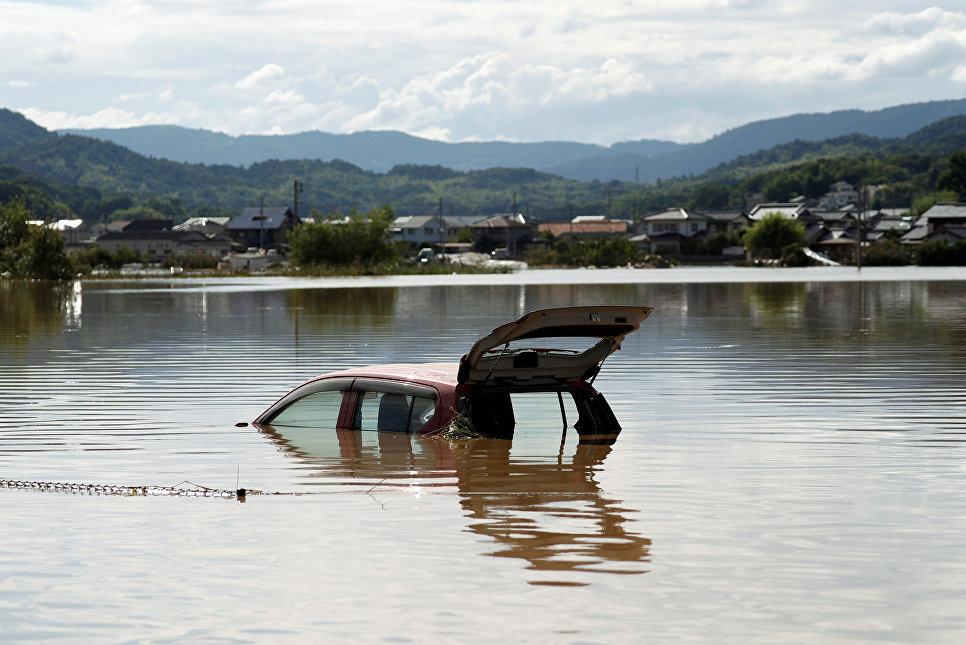 Затопленный автомобиль в городе Курасики, префектура Окаяма, Япония. 8 июля 2018 года