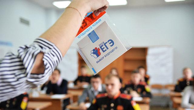 Преподаватель демонстрирует пакет и компакт-диск с заданиями перед началом ЕГЭ. Архивное фото