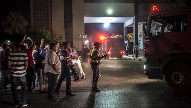 Египетский полицейский регулирует движение у ворот нефтехимической компании Гелиополис после произошедшего ночью взрыва резервуара с топливом. 12 июля 2018