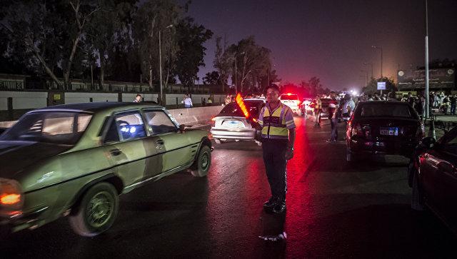 Египетский полицейский регулирует движение на дороге рядом с  нефтехимической компанией Гелиополис после произошедшего ночью взрыва резервуара с топливом. 12 июля 2018