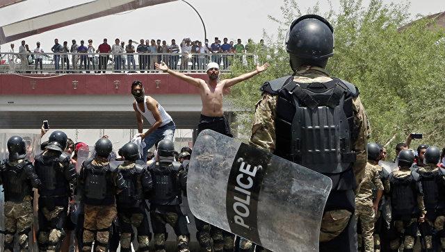 Иракская полиция и демонстранты возле здания администрации провинции Басра на юге Ирака. Архивное фото