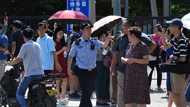 Офицер полиции Китая среди толпы людей собравшихся возеле посольства США в Пекине, где произошел взрыв. 26 июля 2018