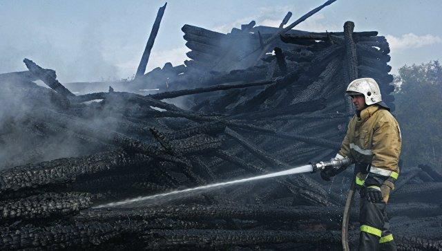 Сотрудник противопожарной службы у сгоревшего здания церкви Успения Божией Матери в Кондопоге в Карелии. Архивное фото