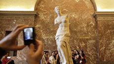 Китайские туристы у скульптуры Венера Милосская в Лувре