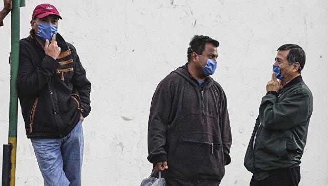 Мужчины, прикрывая лица масками, ждт пока пожарные устранят течь в результате пиратской врезки в газопровод в северной провинции Пуэбла, центральная Мексика. 12 сентября 2018