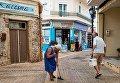 Женщина подметает улицу в городе Малия