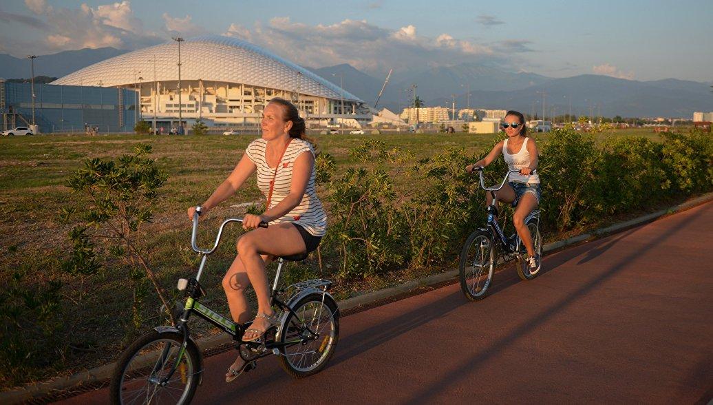 Отдыхающие катаются на велосипедах на набережной в Сочи