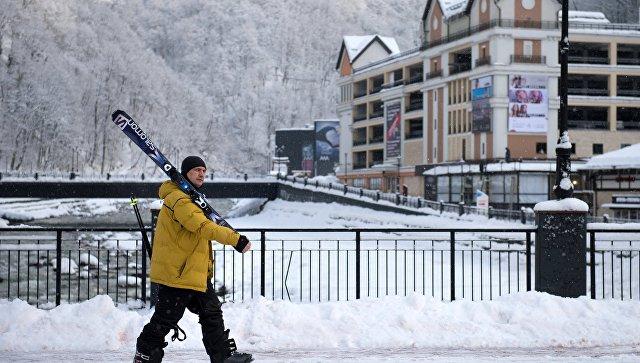 Отдыхающий с лыжами на горнолыжном курорте Роза хутор в Сочинском Национальном Парке