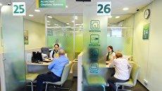 Менеджеры дополнительного офиса по обслуживанию физических лиц ПАО Сбербанк во время работы с клиентами. Архивное фото