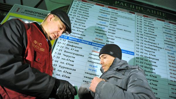 Сотрудник ФМС проверяет документы у мигранта, архивное фото