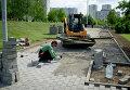 Рабочий укладывает тротуарную плитку. Архив