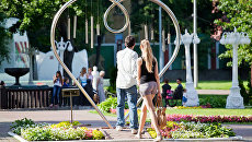 Влюбленная пара проходит через памятник Сердце в саду Эрмитаж