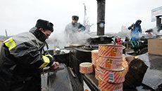 Сотрудники МЧС России готовят пищу на полевых кухнях для прихожан, стоящих в очереди в храм Христа Спасителя