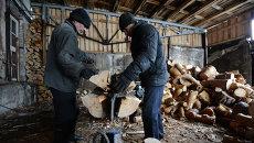 Рабочие перерабатывают на дрова отходы производства на лесопромышленном предприятии Абсолют-М