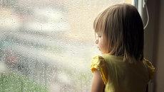 Девочка смотрит в окно. Архив