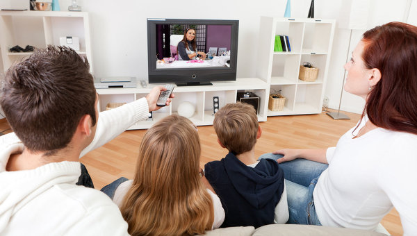 Молодая семья смотрит телевизор