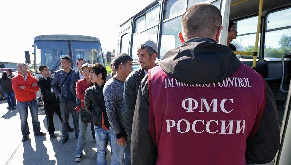 Сотрудник ФМС России с задержанными мигрантами, архивное фото