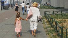 Бубушка с внучкой гуляет по городу