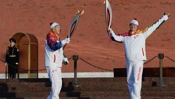 Герой Советского Союза Борис Рунов (слева) передает факел герою России Ивану Нечаеву.