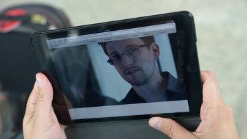 Журналист изучает фото бывшего сотрудника ЦРУ Эдварда Сноудена. Архивное фото