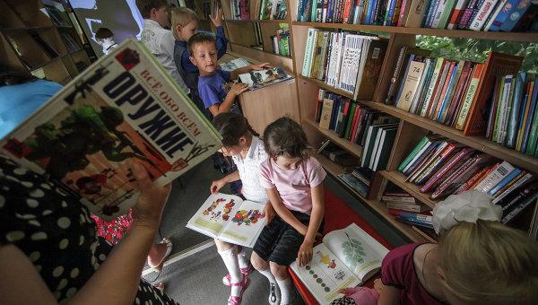 Школьники читают книги  в библиотеке. Архивное фото