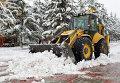 Экскаватор убирает снег на Новособорной площади Томска