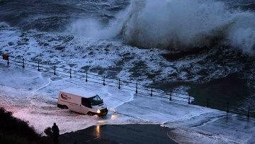 Фургон проезжает сквозь воду во время шторма на севере Англии
