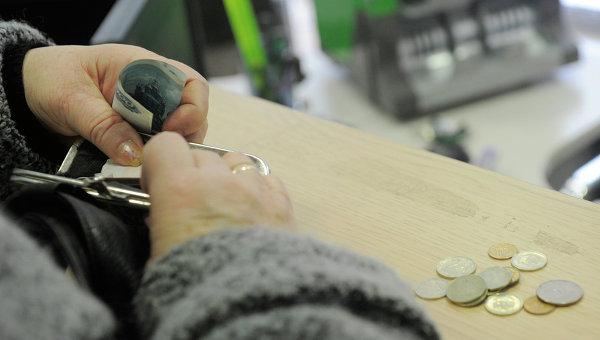 Женщина расплачивается в кассе, архивное фото