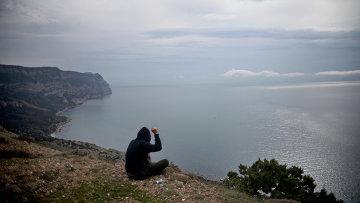 Молодой человек на скалистом побережье Черного моря