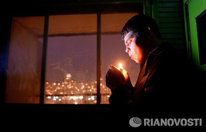 Молодой человек курит в подъезде жилого дома