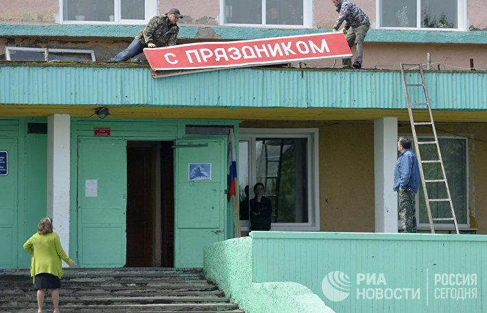 Демонтаж плаката С праздником на Доме культуры в поселке Ключи Камчатского края.